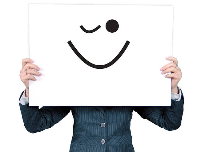 Woman holding poster with winking emoji